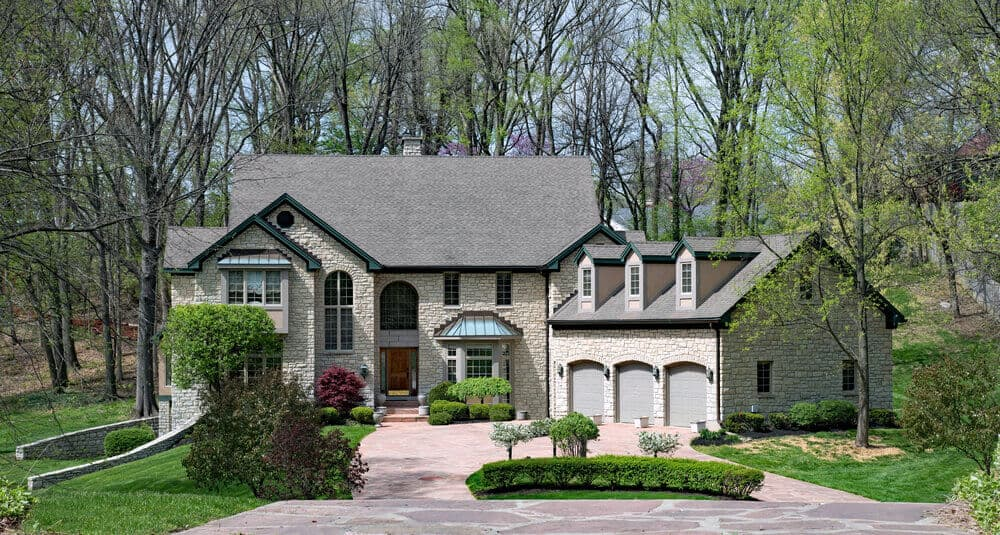 A big, luxury stone house with a three-entrance garage. The house is surrounded by woods and trees at the back and its front area is landscaped beautifully.