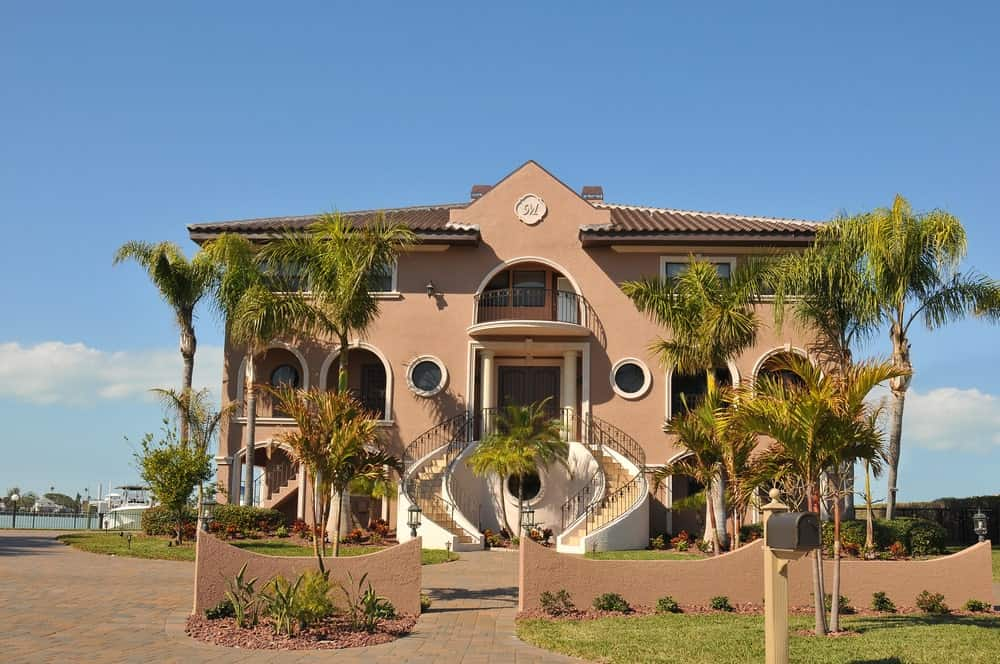 Three-story brown stucco luxury waterfront house with arches, balconies, and an exterior bifurcated staircase.