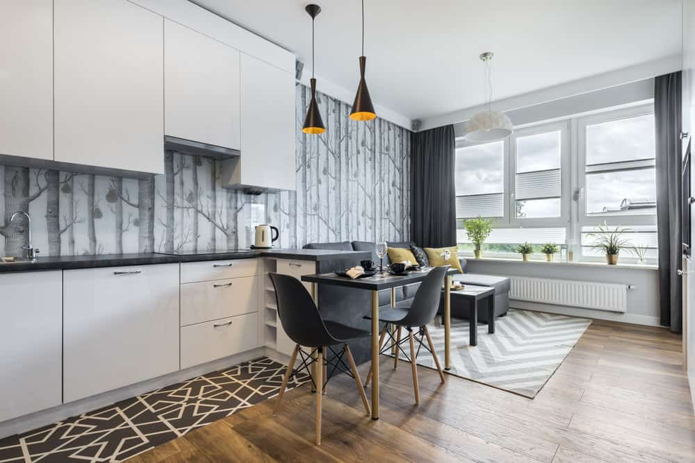 White and black small kitchen with tiny peninsula off of which extends a cozy black dining table for 3 people. Living room adjacent to the kitchen - overall nice open concept living space.