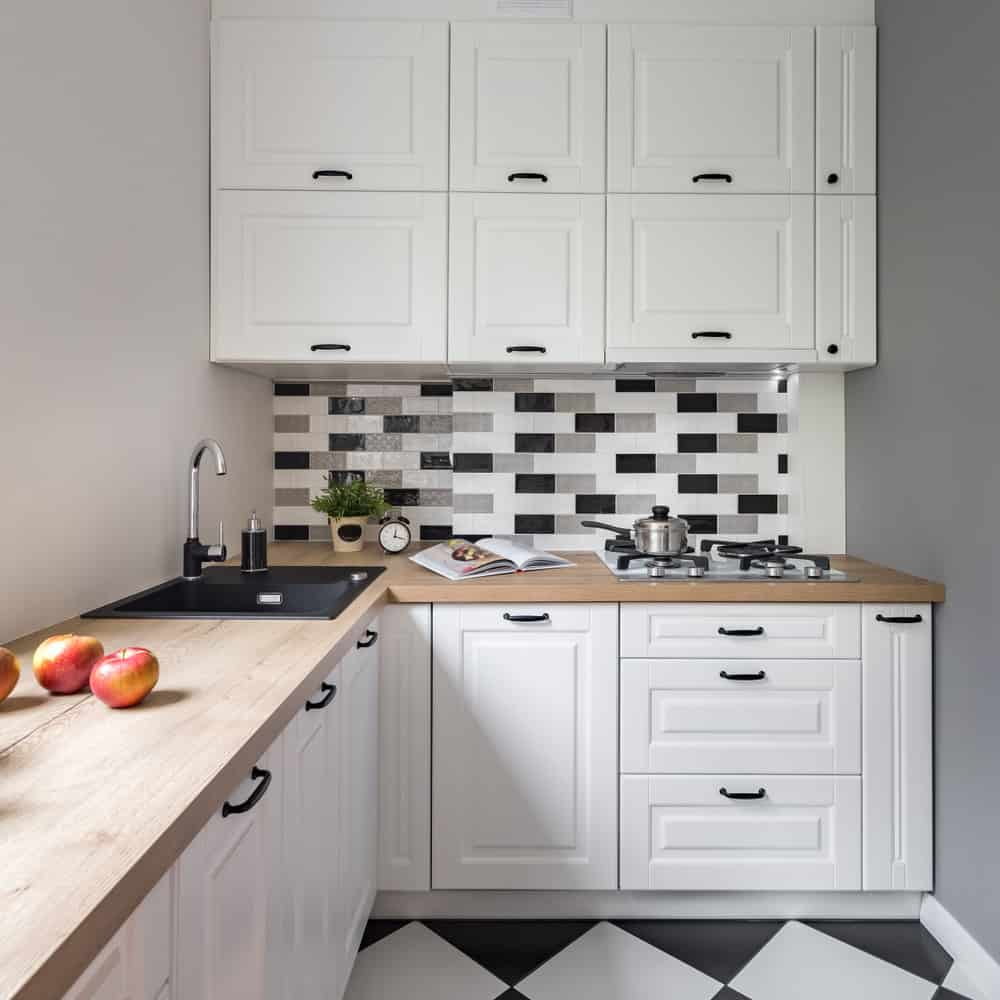 The wood countertop and checkered backsplash make this tiny kitchen a winner. I'm not too crazy about the engraved cabinets (shaker style would look better) but the black and white backsplash and floor look amazing.