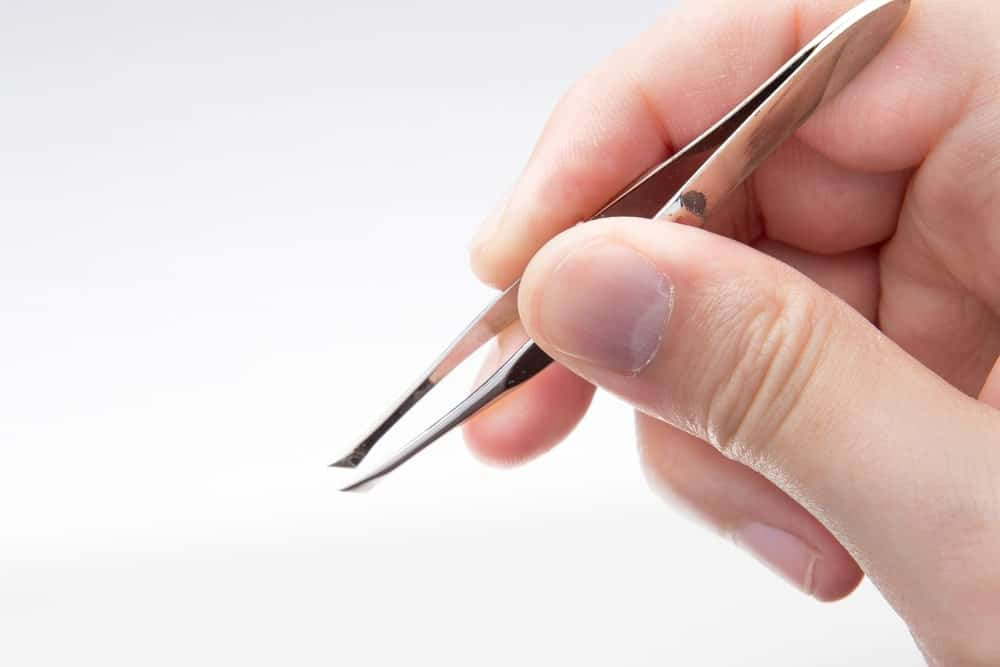 Hand holding a tweezers on white background.