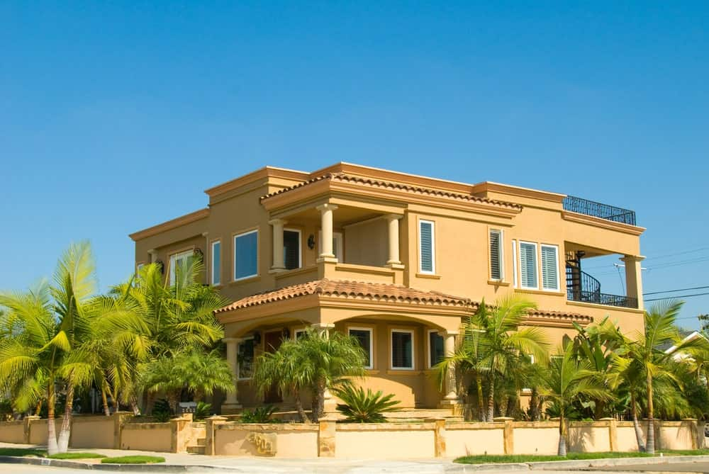 Large two-story yellow stucco house with private enclosure and palm trees.