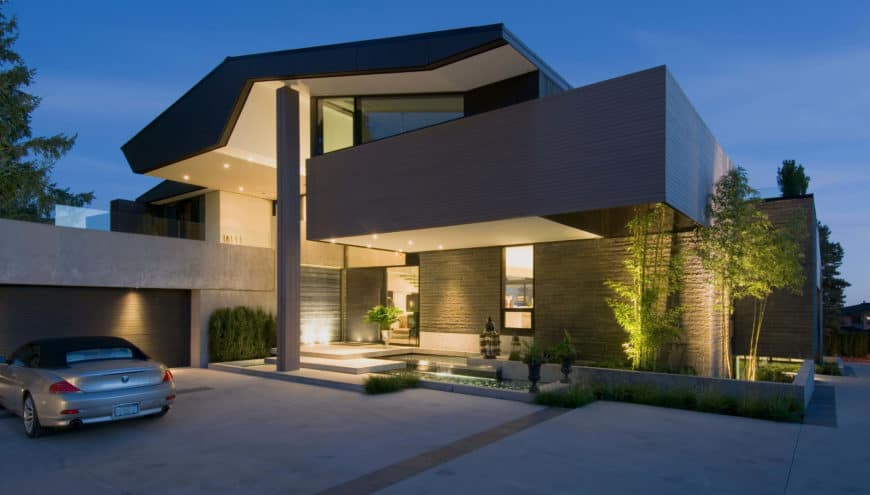 This jaw-dropping modern gray house boasts a large garage area along with a wide driveway.