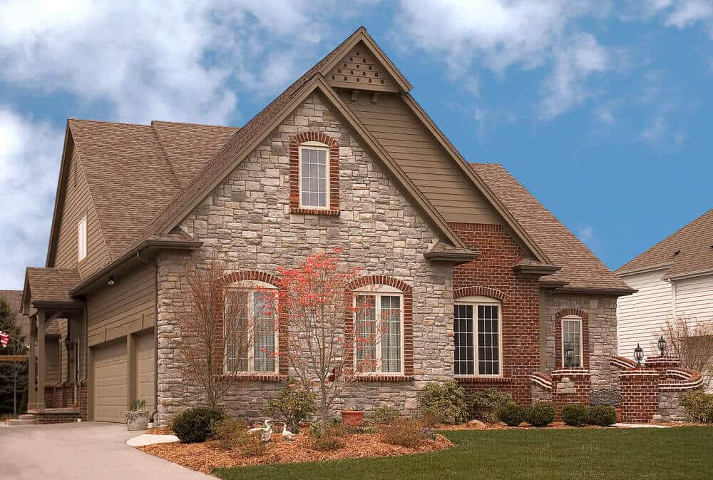 A warm-toned stone house with its windows highlighted with some bricks for an extra style.