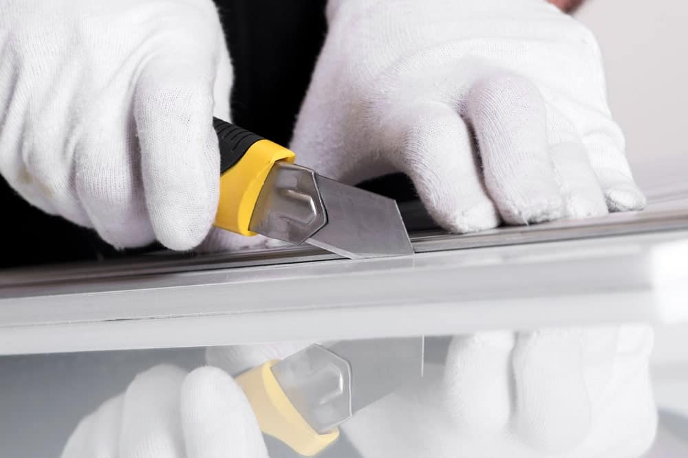 A pair of hands in white cloth gloves holding a utility knife and a piece of foam on the other.