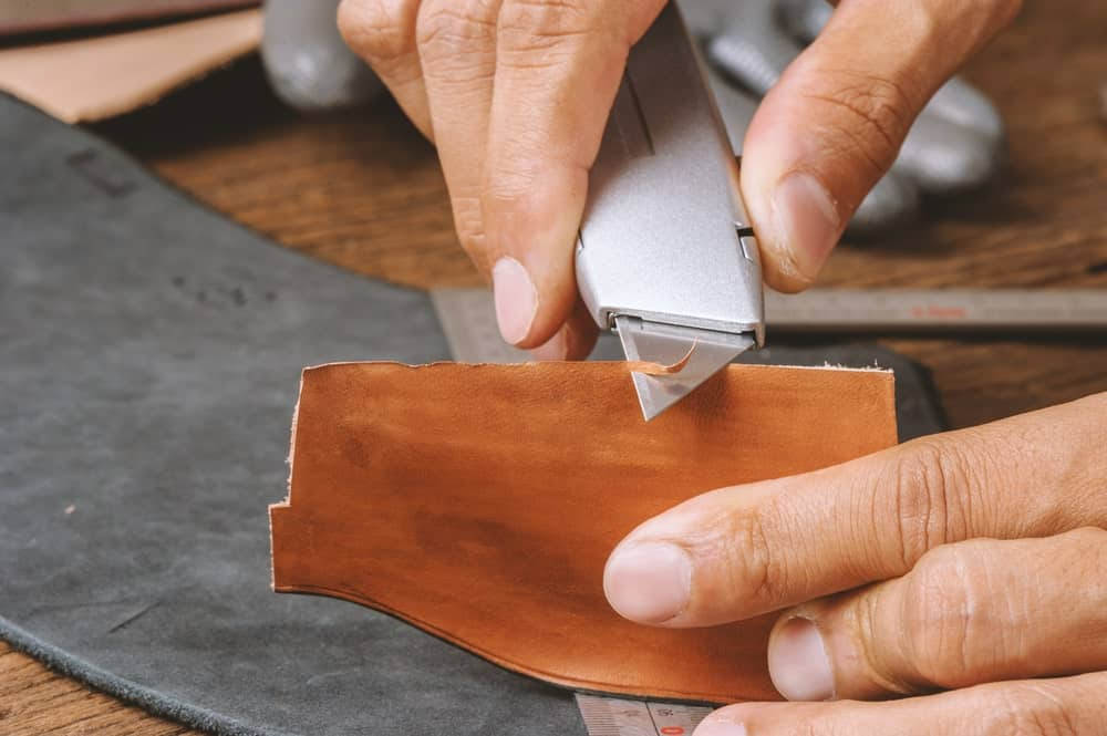 Cutting leather with a retractable utility knife.