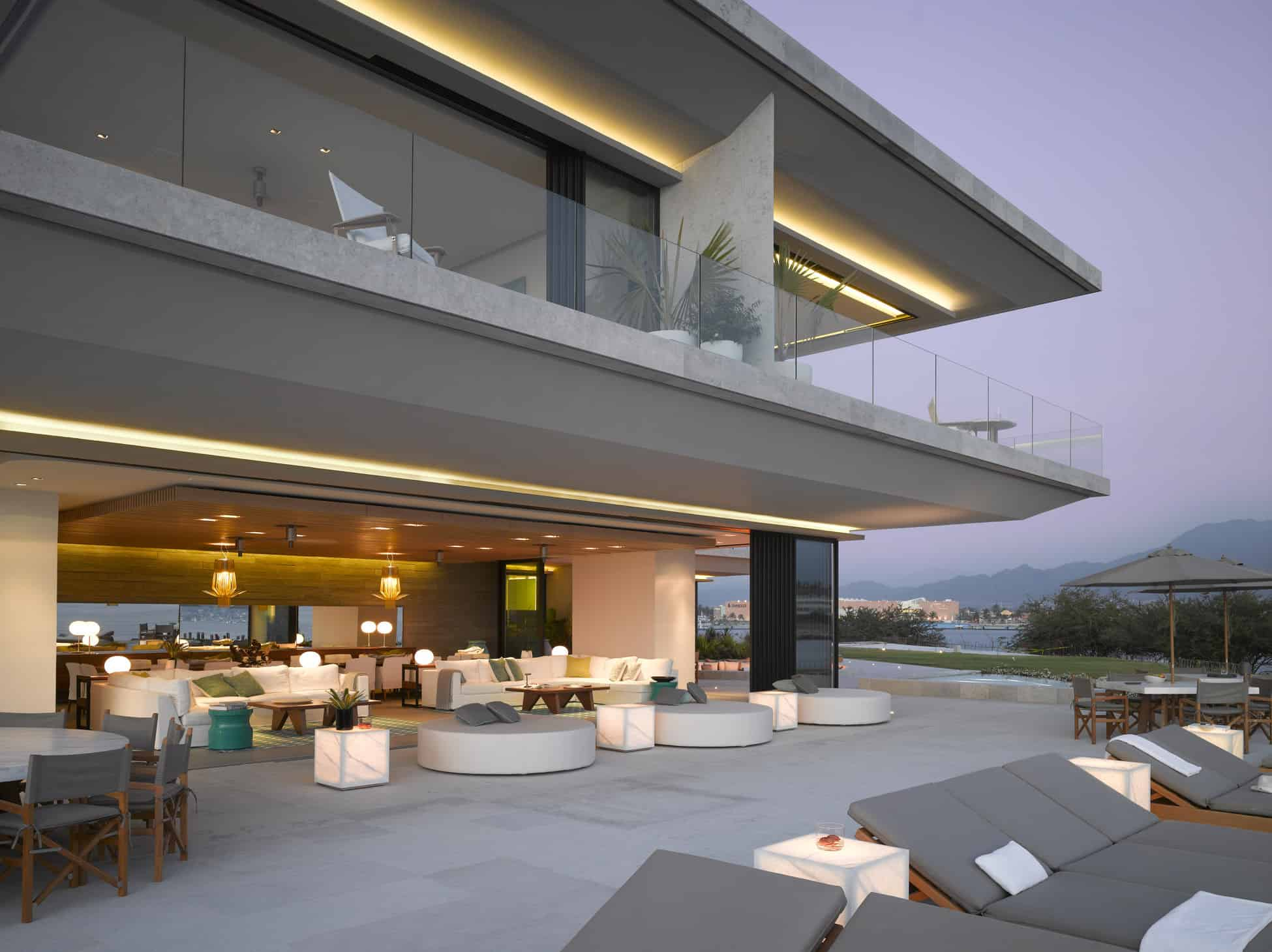 A huge modern house with gray exterior and an open concept indoor. The outdoor area boasts amazing amenities as well.