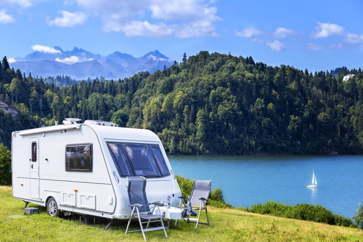 An RV is parked with outdoor table and chairs is parked with full view of the mountains and lake.