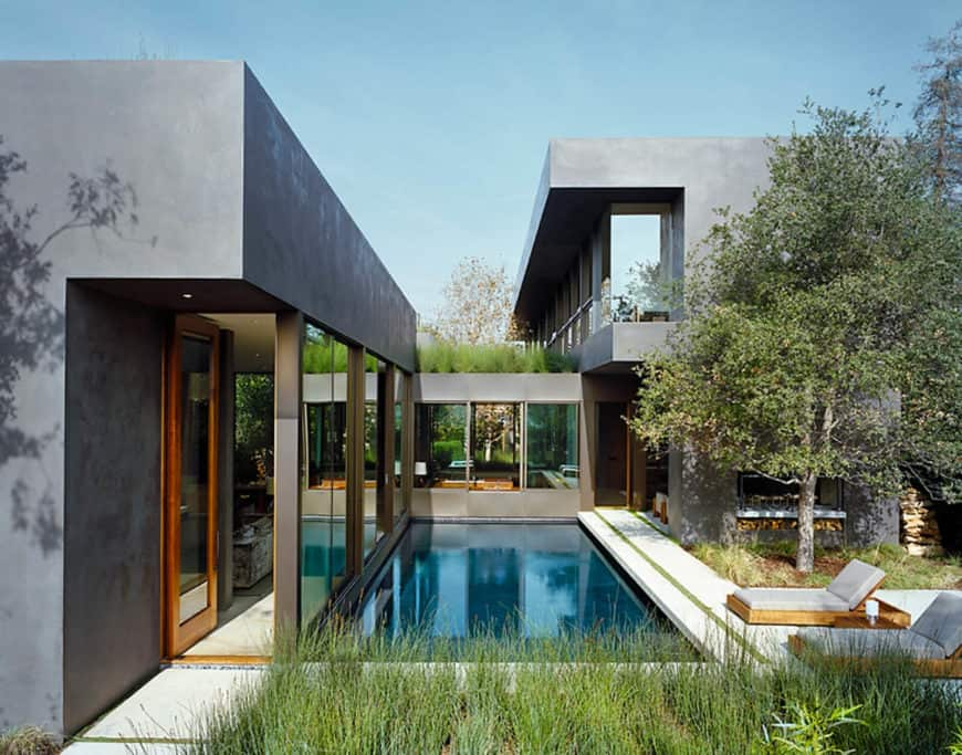A gray-exterior house with a swimming pool featuring two sitting lounges on the side.