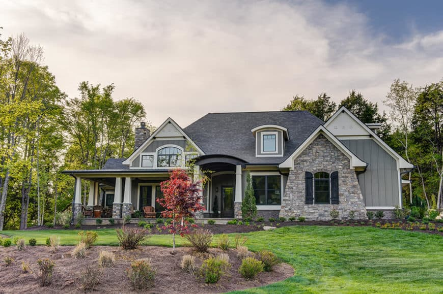A luxurious home featuring a gray exterior, glass windows and a beautiful and relaxing garden and frontyard area.