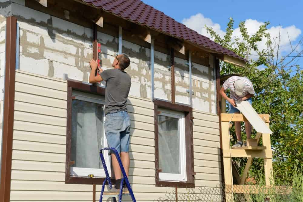 Two men working on installing vinyl panels as exterior siding to the house.