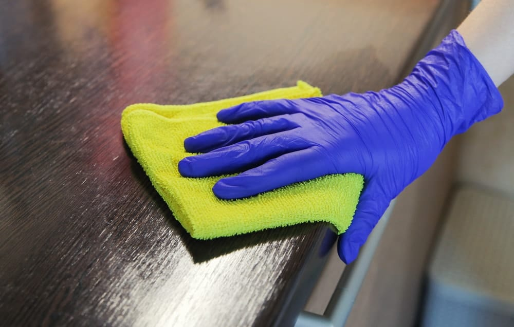 Hand wearing purple rubber gloves seen wiping off a wooden countertop with the use of green microfiber washcloth.