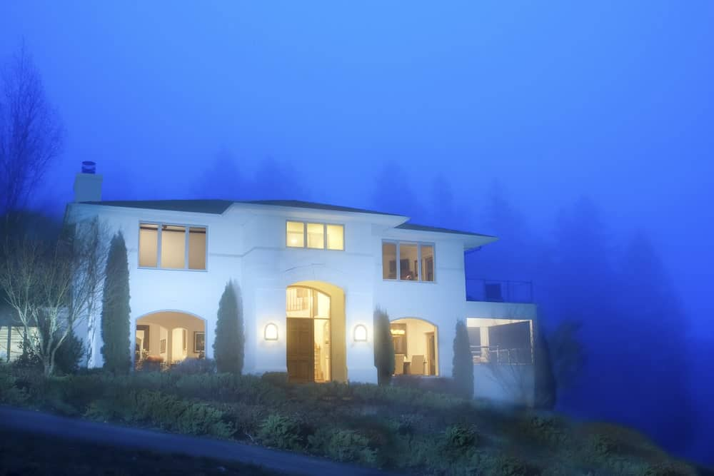 White modern stucco house on a hilltop seen during twilight.