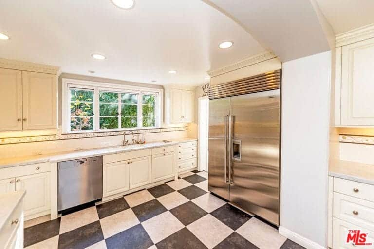 Another look at the kitchen featuring the checker tiles flooring, recessed lights, white cabinetry and stainless steel appliances.