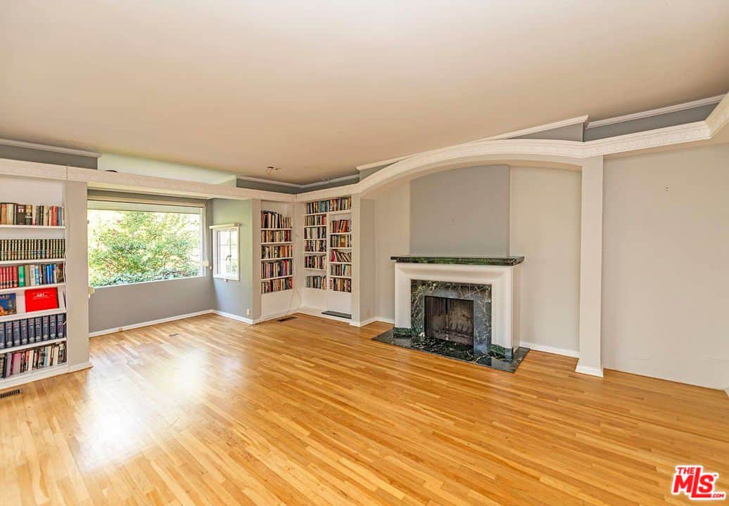 This room features a fireplace and bookshelves perfect for a library room.