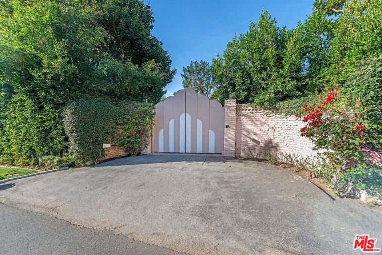 The property's gate and fence is surrounded by beautiful greenery.
