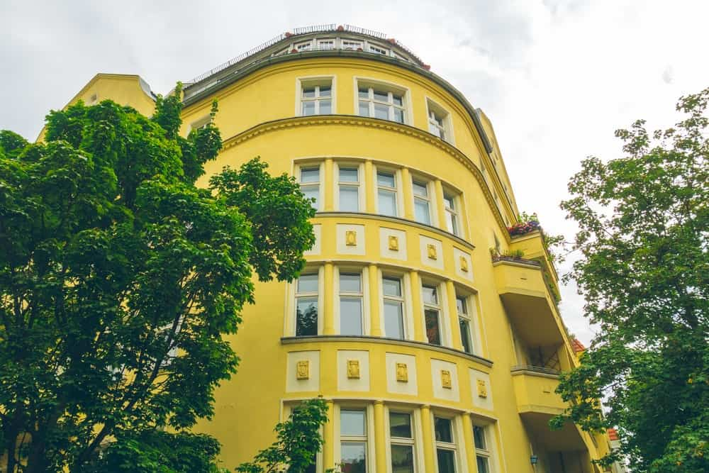 Multiple-story European corner house with yellow stucco exterior.