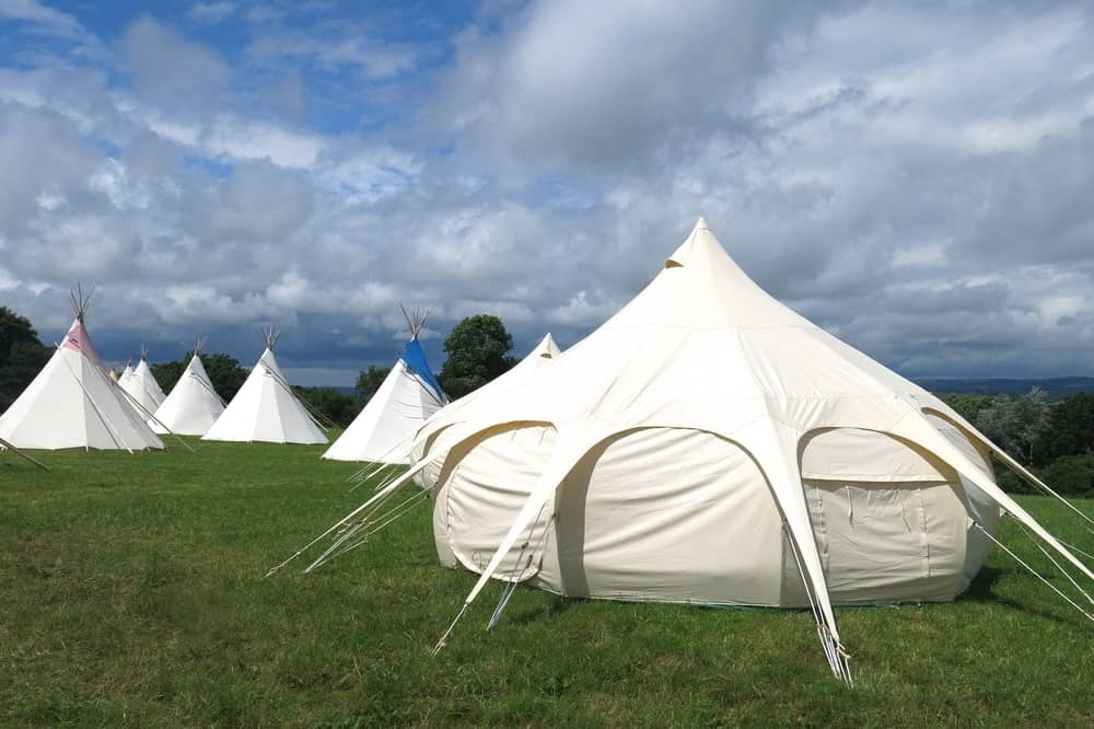 White tents and yurts on campsite.