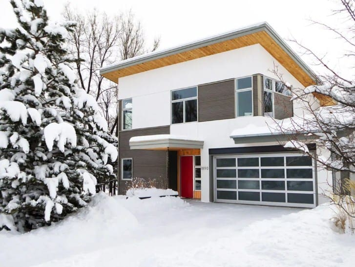 A modern house with a gray exterior, covered in snow.