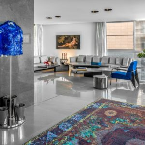 Super cool contemporary condo living room with large grey sofas and bright blue accent chair