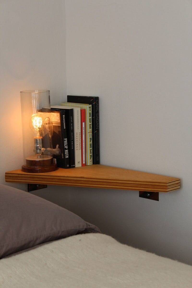 Here's a corner floating shelf serving as nightstand