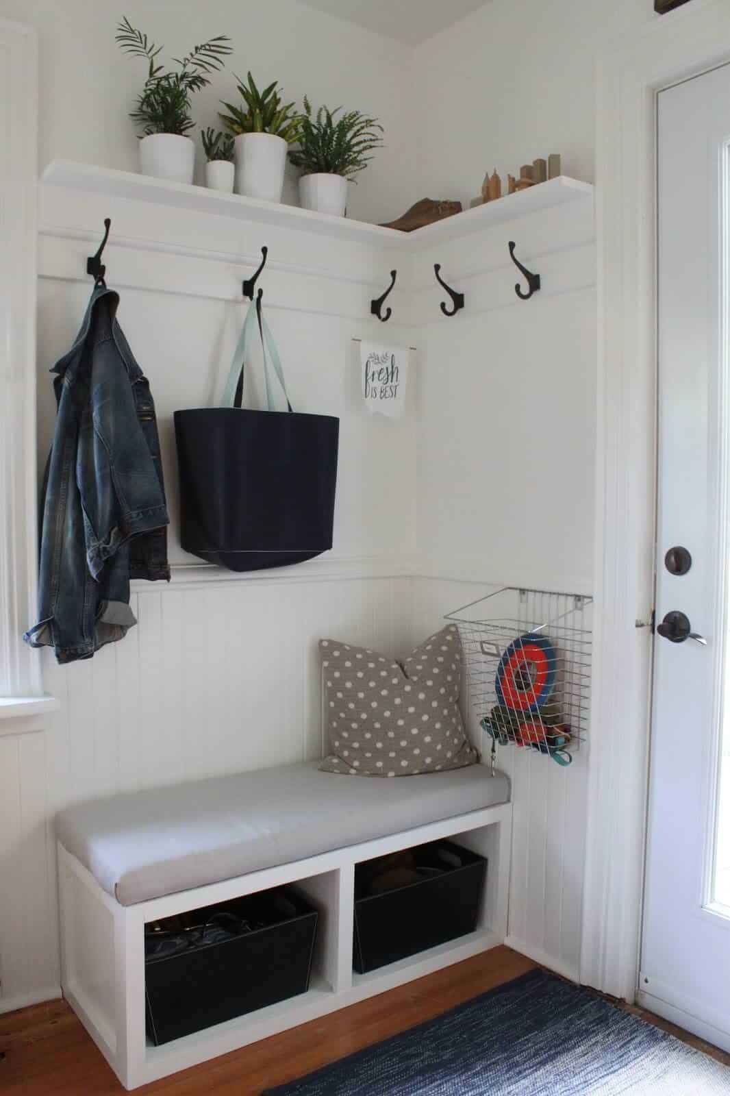 Mudroom with small storage bench, attractive hooks and upper floating shelf.