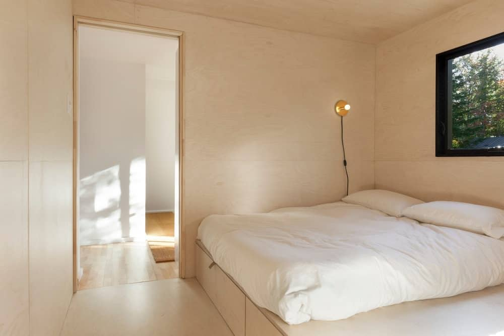Simple guest bedroom with minimalist design showcases a built-in platform bed lighted by a brass wall sconce.