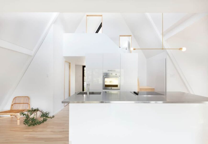 White modern kitchen with stainless steel counter in A-frame cabin with loft.