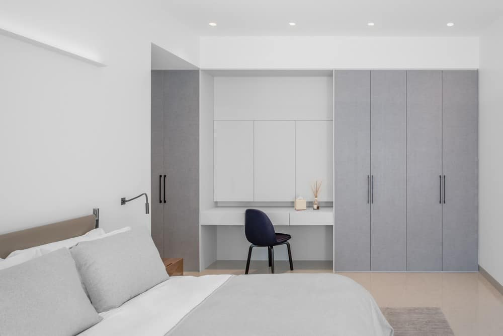 Minimalist master bedroom with built in wardrobe and desk in condo apartment.