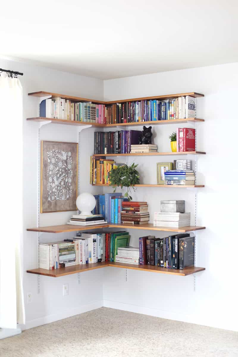 Large floating shelves fitted for a corner offers plenty of book storage. You could extend this concept to create a small home library
