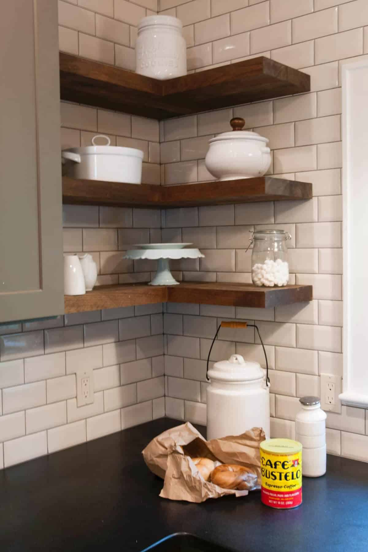I like the natural wood floating shelves against the shiny subway tile backsplash.