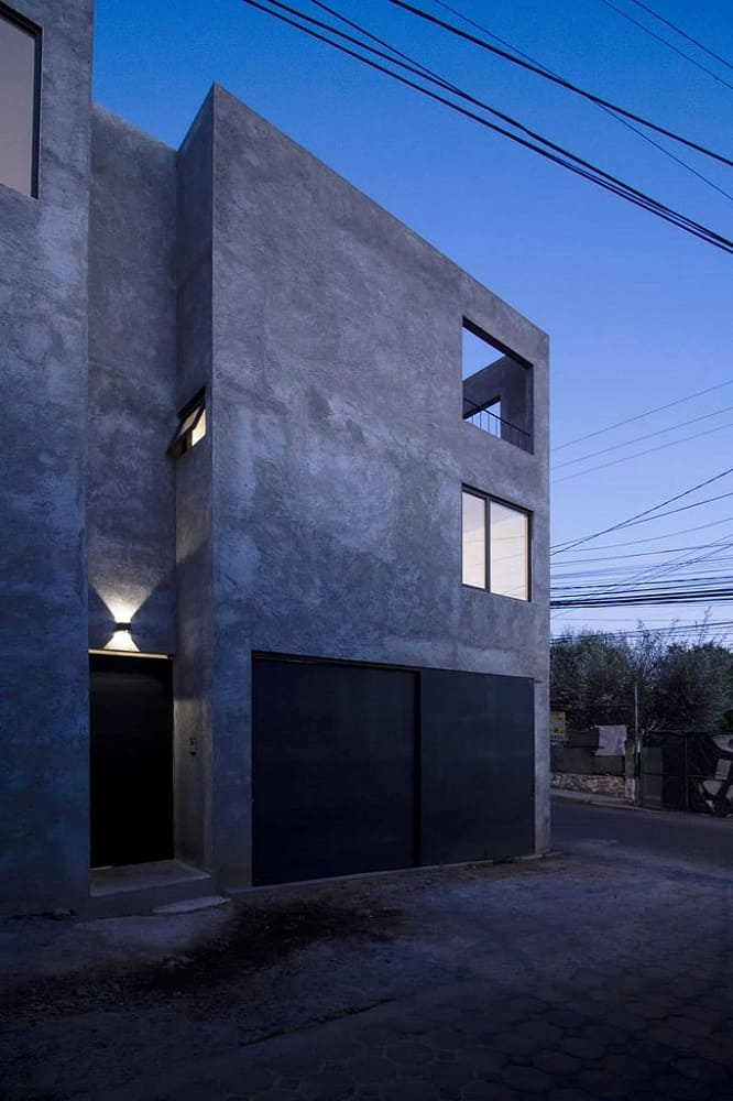 This is a front view of the large multi-level concrete home with large concrete exterior walls complemented by the dark main door and garage doors as well as the warm lighting coming from the windows and outdoor lights.