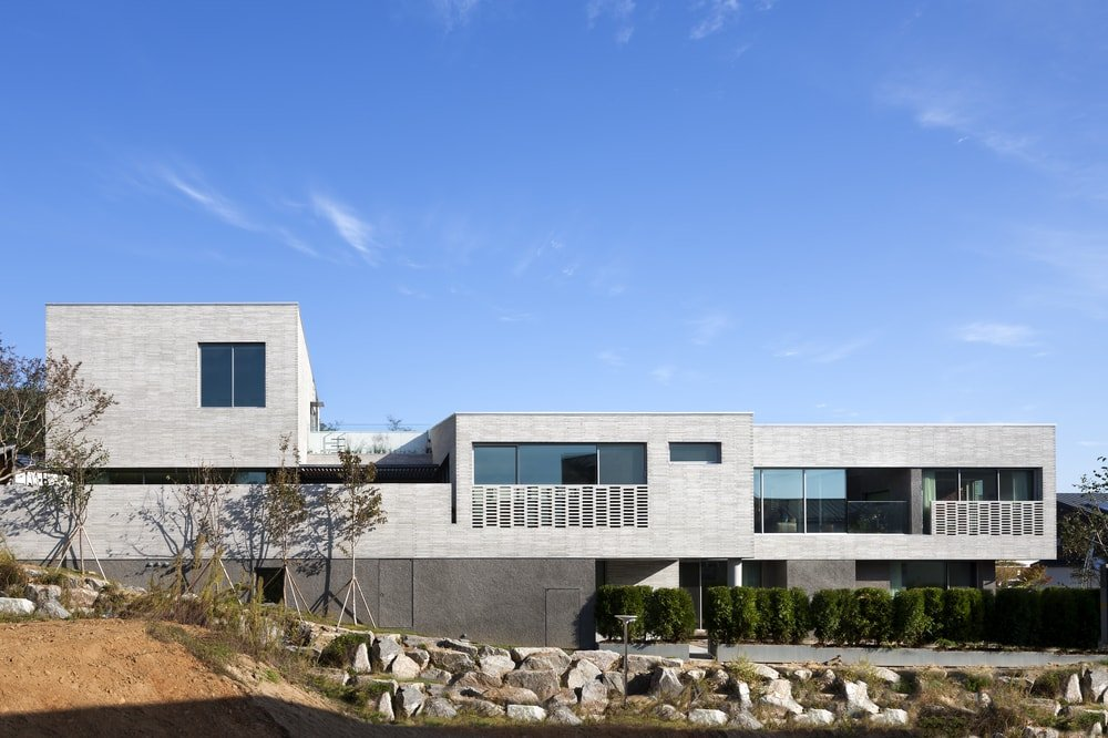 This is a look at the elevation of the large concrete house that has an abundance of glass walls and windows that break the solid concrete tones of the house.