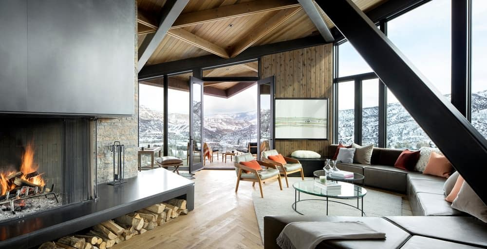 Formal living room with tall ceiling, amazing view and huge custom built sectional sofa facing large modern wood fireplace in modern ski chalet