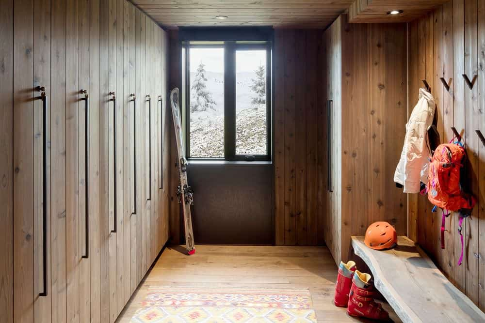 Entryway mudroom with ski holders mounted on the wall as well as many coat hooks and long wooden bench
