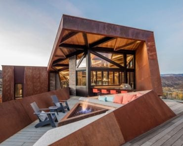 Large deck with a triangle gas firepit and built in sectional sofa
