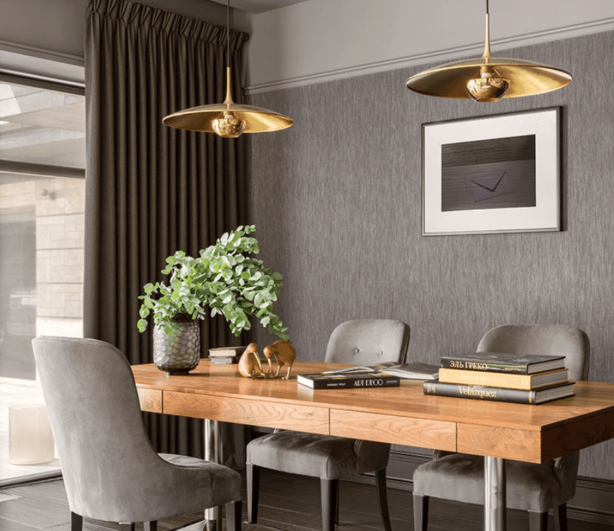 A close up look at this elegant wooden office table set on the room's hardwood flooring and is lighted by classy pendant lights.
