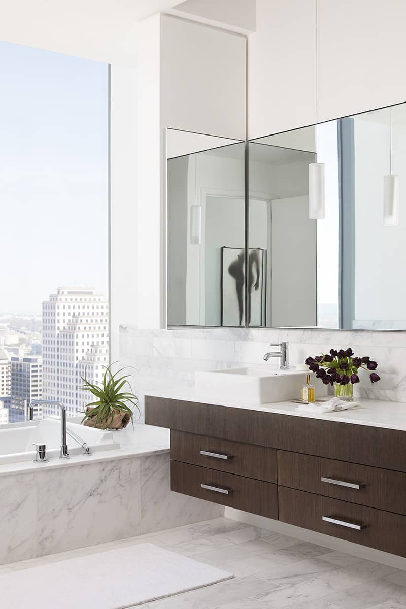 Condo primary bathroom with floating vanity and massive picture window next to marble faced tub