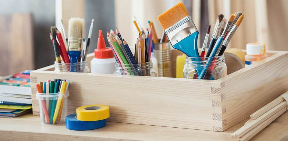 Wooden box with painting and drawing craft supplies such as pencil crayons, colorful tape and glue.