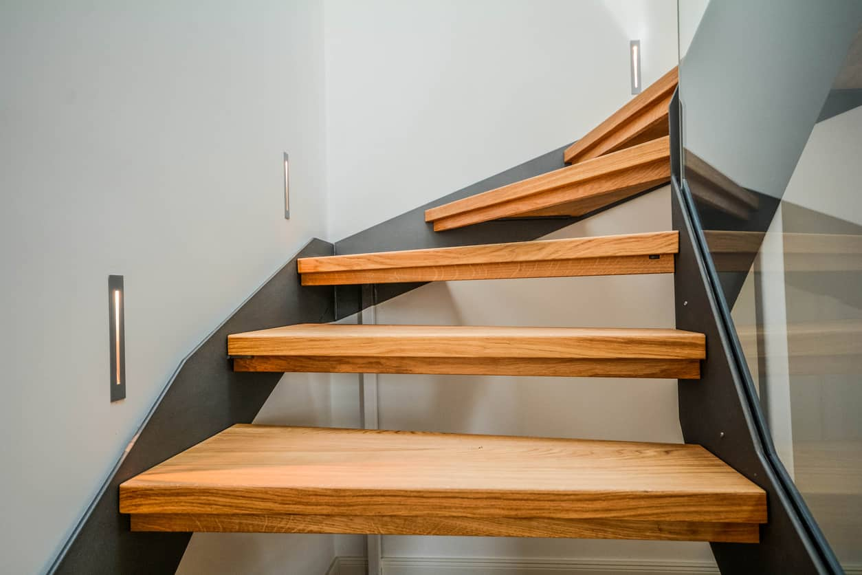 Close-up of wood tread stairs with steel riser and glass railing in modern home.