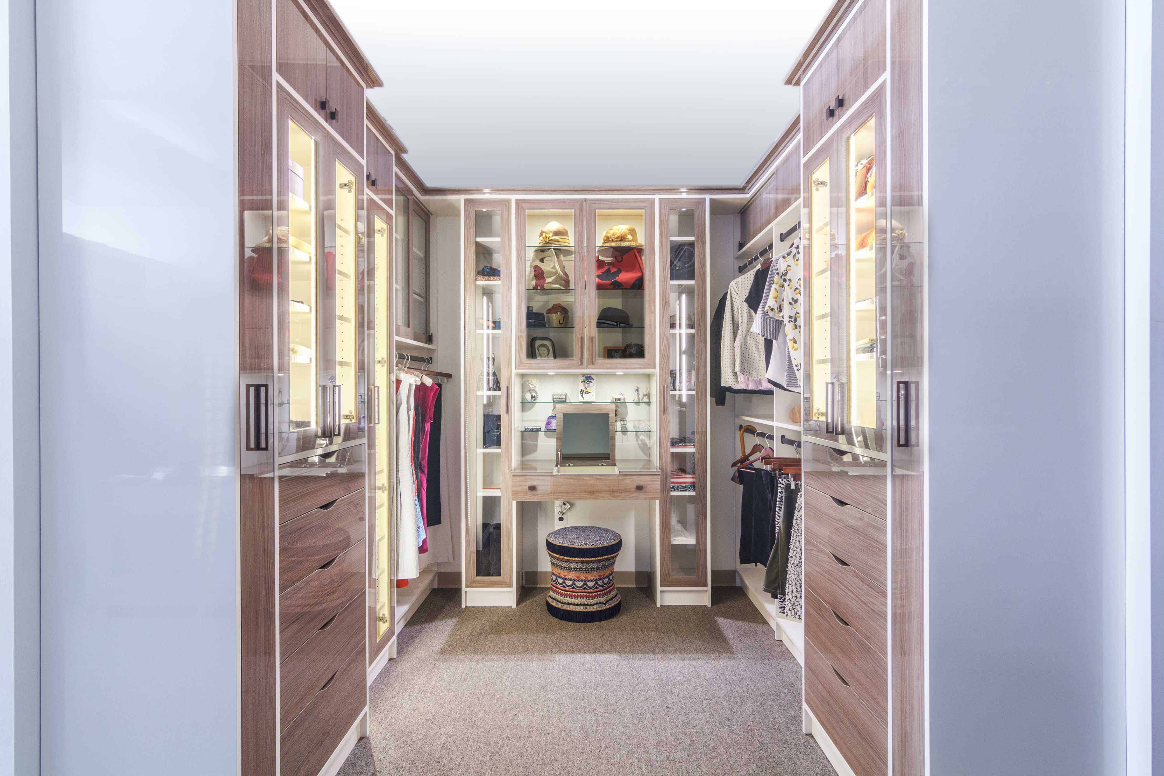 Glamorous walk-in closet with glass-faced storage cabinets, built-in vanity and plenty of apparel storage by Closet Works.