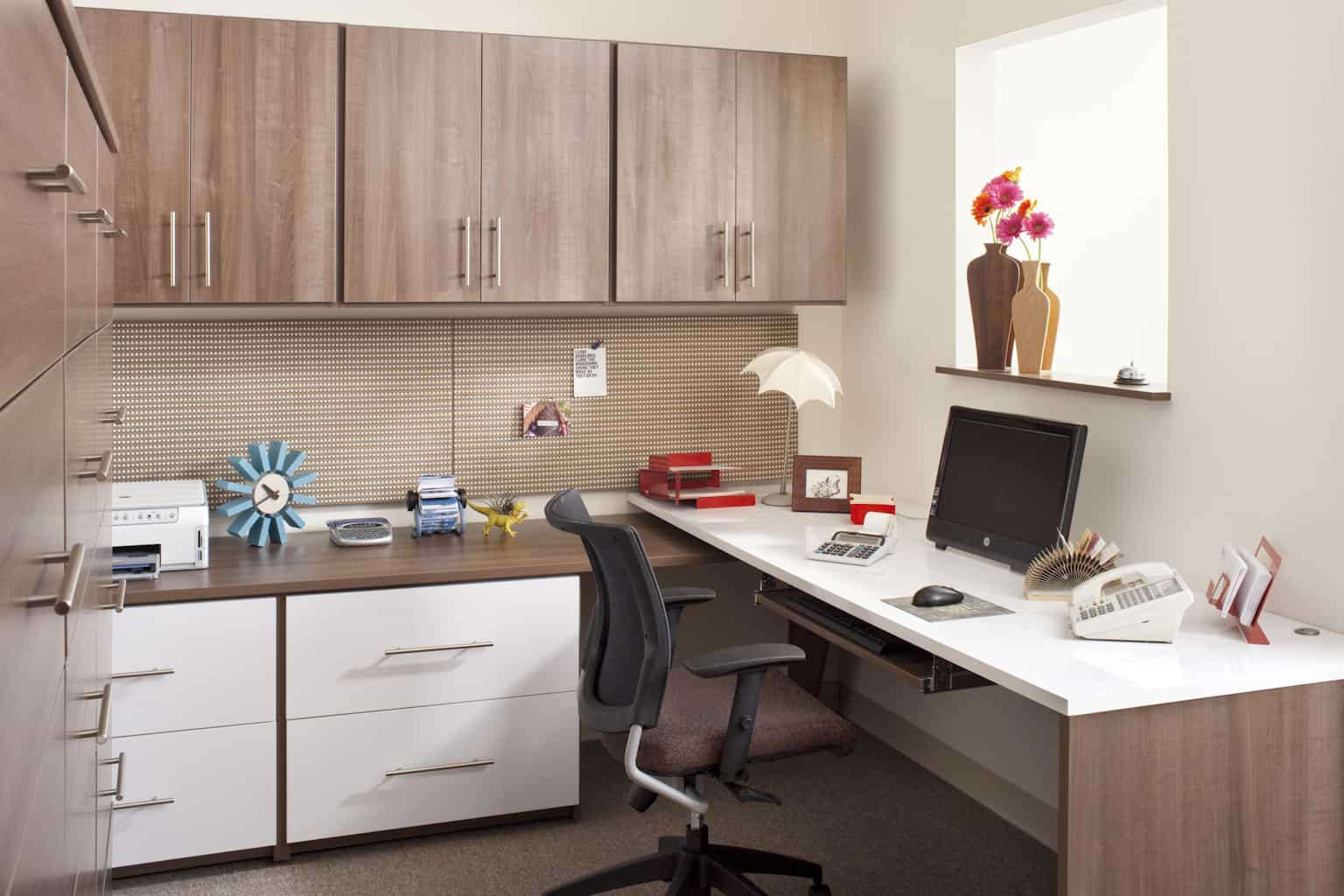 A chic home office with carpet flooring and classy cabinetry and counters. The office desk looks charming as well.