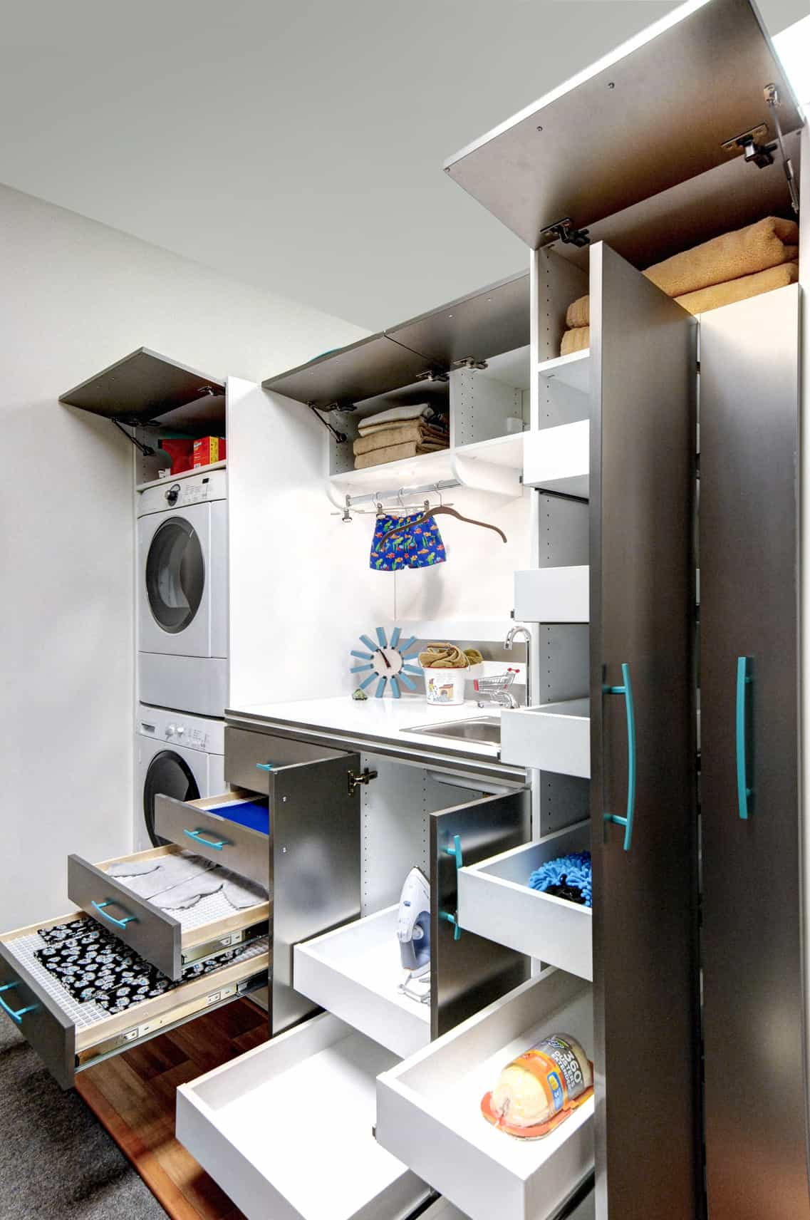 If any room can use clever storage, it's the laundry room. Here's a great custom laundry room cabinet system built nexed to stackable washer and dryer.