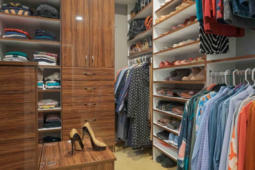 This walk-in closet maximizes its storage potential despite its small size. The sleek wooden armoire and shelves that extend all the way to the top are the ultimate way to house all your clothes and shoes in a small space.