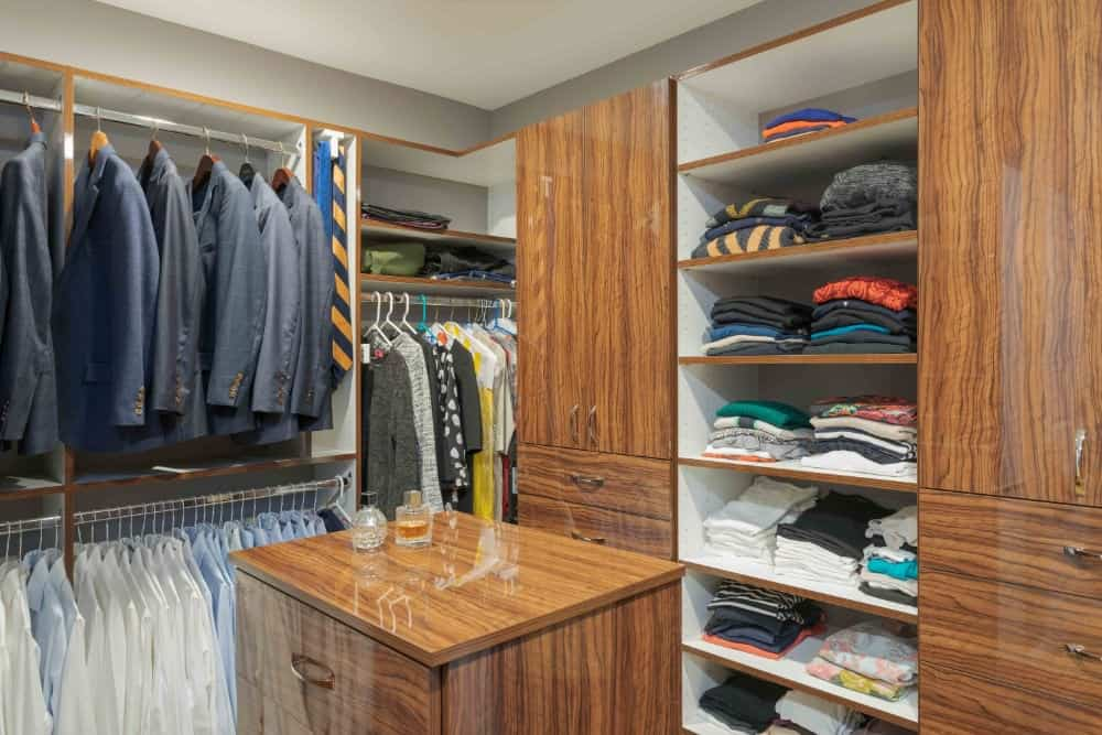 Walk-in closet with small dresser island and two rows of hanger storage for suits and dress shirts.