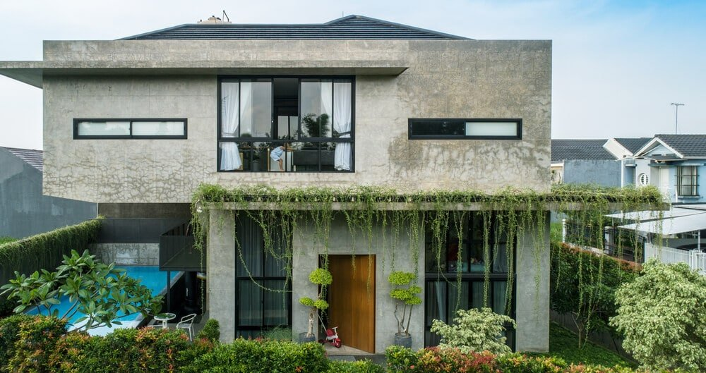 This is a look at the front of the house that has concrete exterior walls adorned by the various windows and glass walls along with hanging vines and landscaping of shrubs.