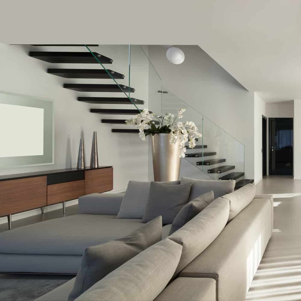 Floating modern space-saving staircase rising above living room.