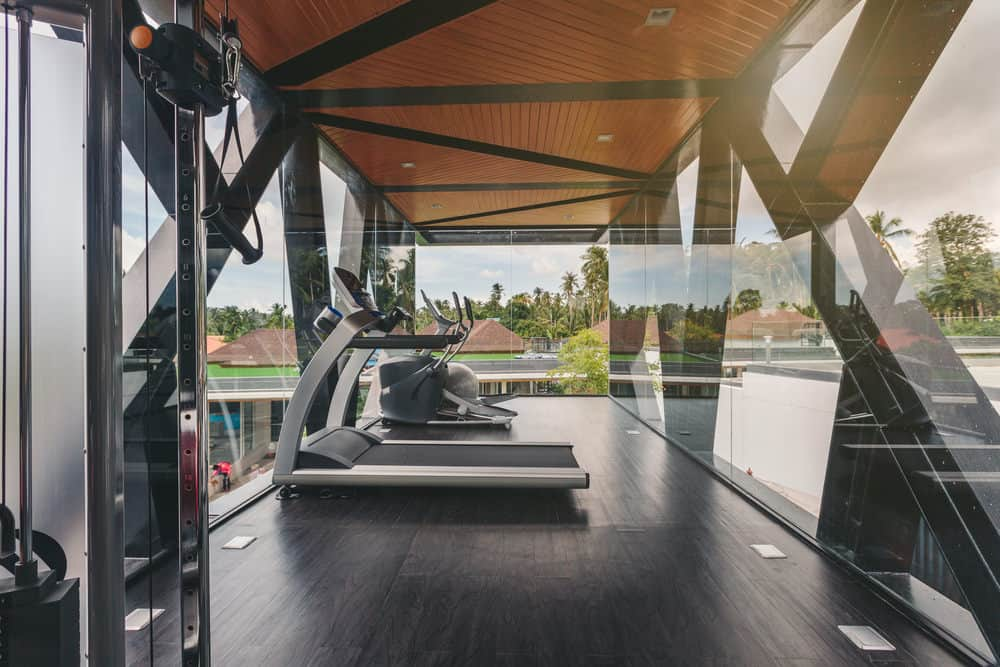Modern home gym with floor-to-ceiling windows and wooden ceiling and flooring.