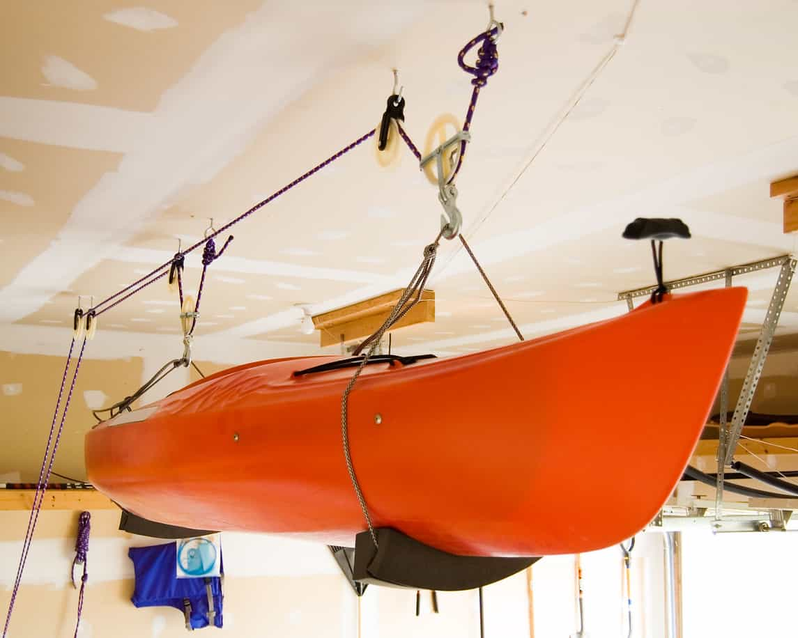 Kayak stored suspended from garage ceiling with kayak storage pulley system