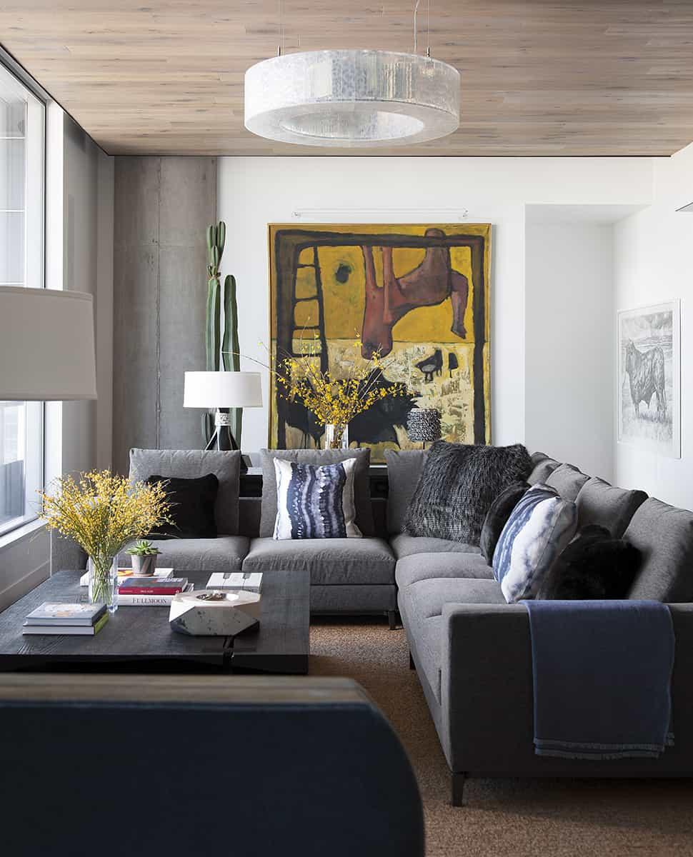 A huge round chandelier on a wooden ceiling hung over a gray L-shaped sofa wrapped around a large wooden center table. A large canvas painting added a pop of color.
